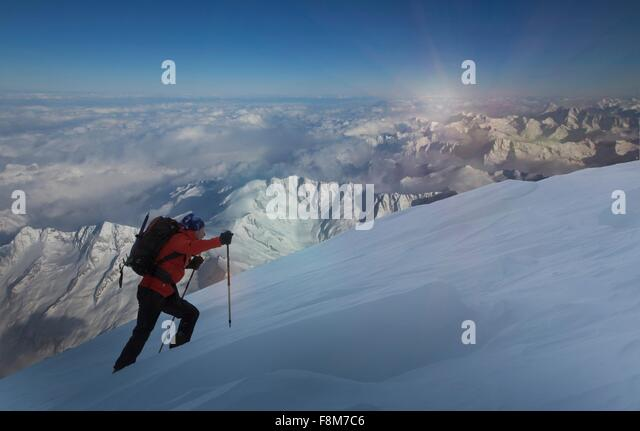 Climber moving up through deep snow, Swiss Alps, Canton Wallis, Switzerland - Stock Image