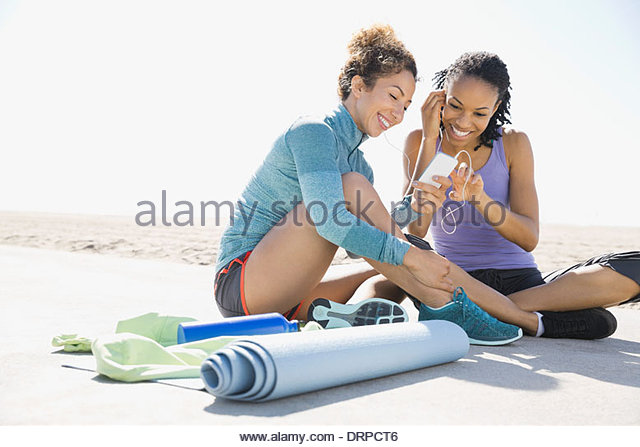 Active women listening to music on beach - Stock Image