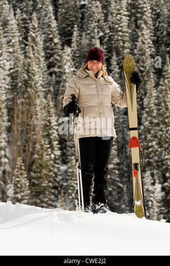 A smiling woman standing with skis in front of snow covered trees, San Juan National Forest, Silverton, Colorado. - Stock Image