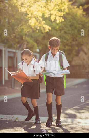 School kids reading books while walking in campus - Stock Image