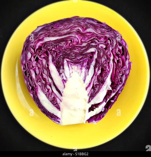 Half of a split cabbage on a yellow plate.. - Stock Image
