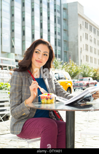 Mixed race woman eating lunch at urban sidewalk cafe - Stock Image