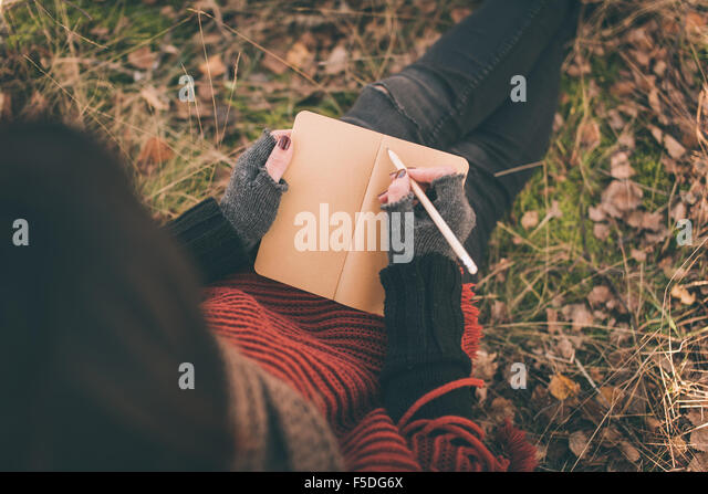 Woman in nature writing in a notebook - Stock-Bilder