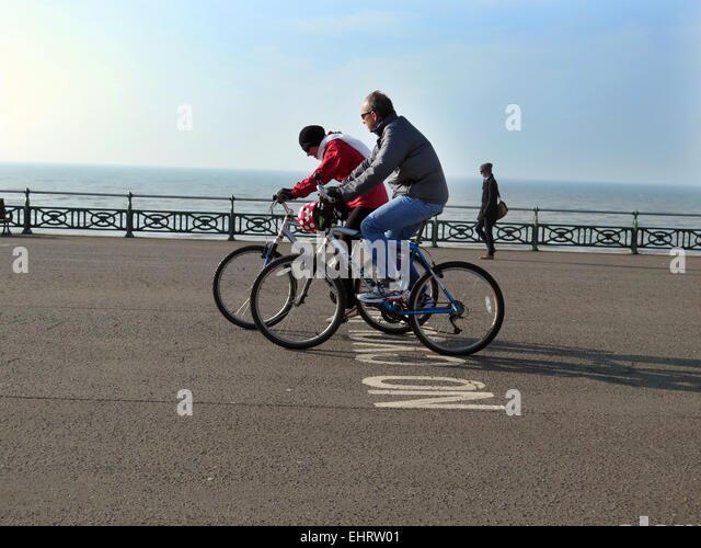 Two Cyclists, not wearing crash helmets, ignore a NO CYCLING sign painted on the tarmac while cycling on Hove promenade - Stock Image