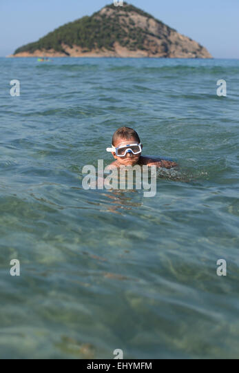 Boy wearing goggles swimming in the sea - Stock Image