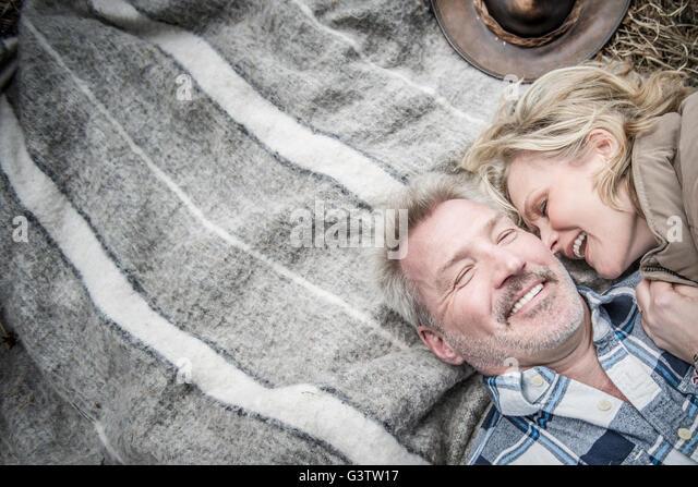 Senior couple cuddling together on a blanket at their campsite. - Stock-Bilder
