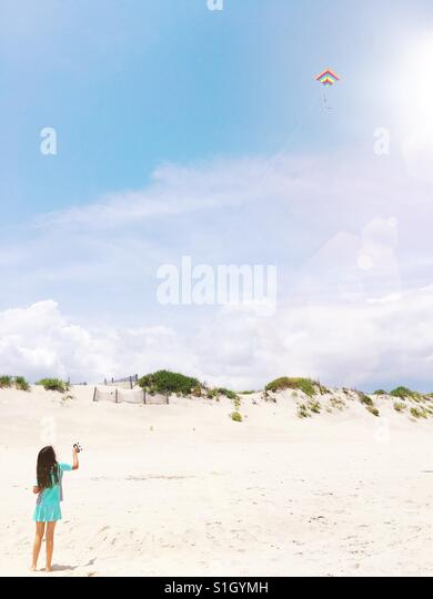 Girl flying a kite on the beach. - Stock-Bilder