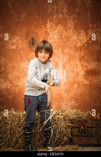 Boy with pitchfork standing by a hay bale, Morocco - Stock Image