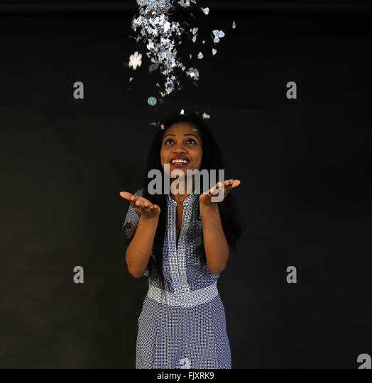 Cheerful Woman Throwing Decorative Objects Against Colored Background - Stock Image