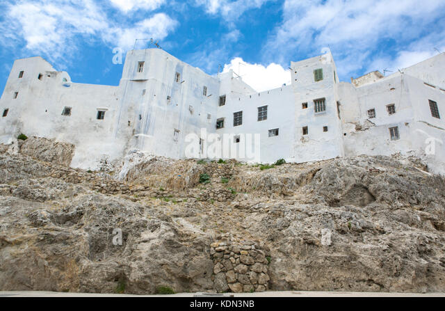 Houses built over coast rocks with traditional whitewashed exterior. Tetouan, Morocco. - Stock Image