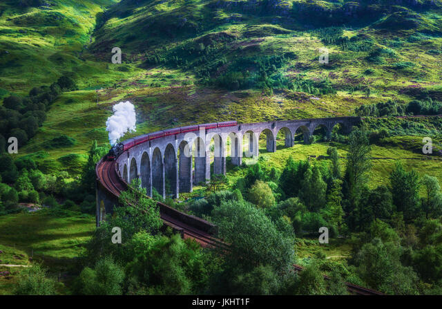 Glenfinnan Railway Viaduct in Scotland with the Jacobite steam train passing over. Artistic vintage style processing. - Stock Image