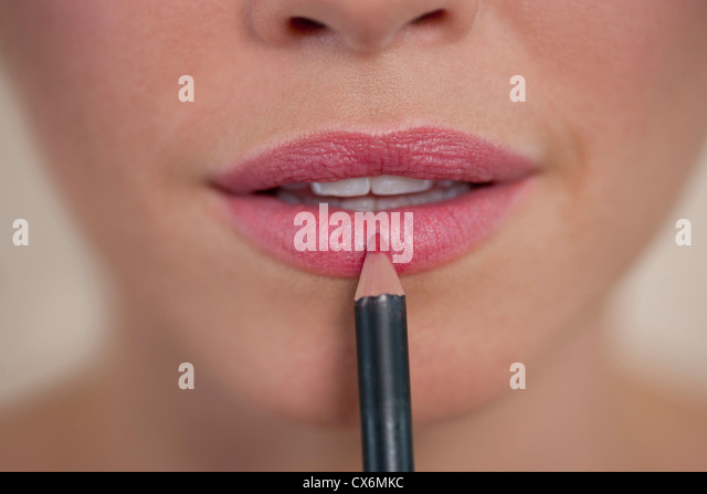 A young woman applying lip liner, showing lower section of face - Stock Image