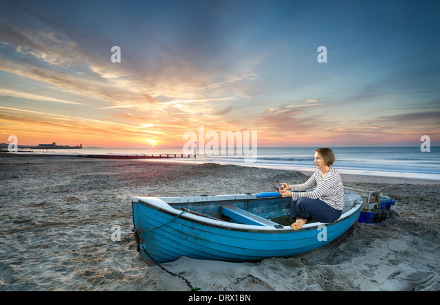 Mature woman in 50's using tablet device at sunrise on an idyllic beach - Stock Image