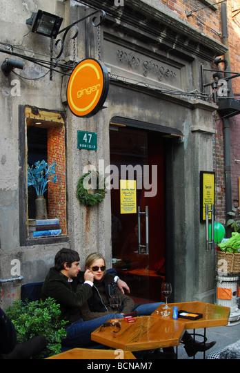 Foreign couple cuddling outside of a trendy restaurant on Taikang Artistic Lane, Shanghai, China - Stock-Bilder