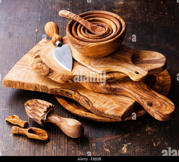 Olive wood tableware on dark wooden background - Stock Image