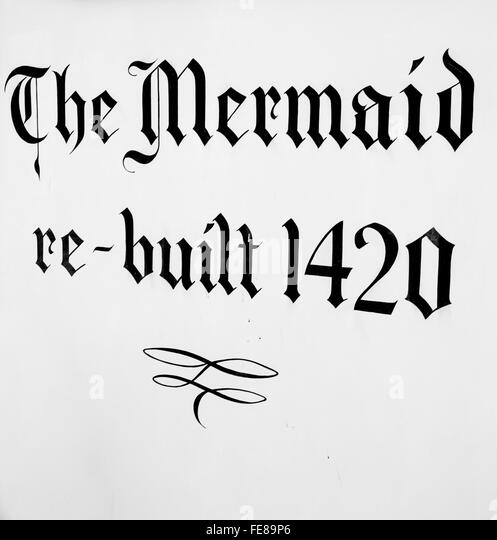 Sign painted on the building of The Mermaid Inn in Rye, East Sussex, UK. Rebuilt in 1420, now a popular inn and - Stock Image