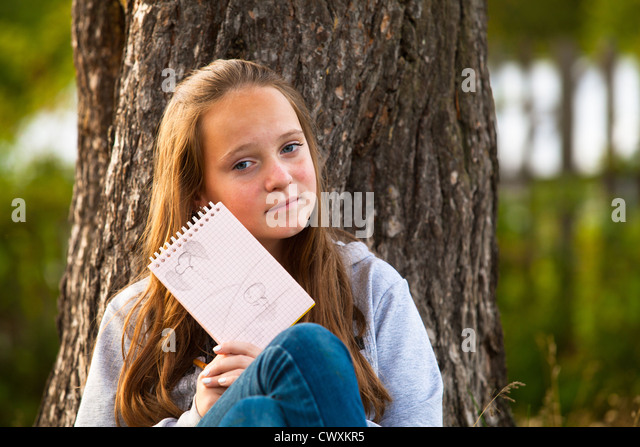 Teen-girl shows notebook while sitting in the park (looks into the camera) - Stock Image