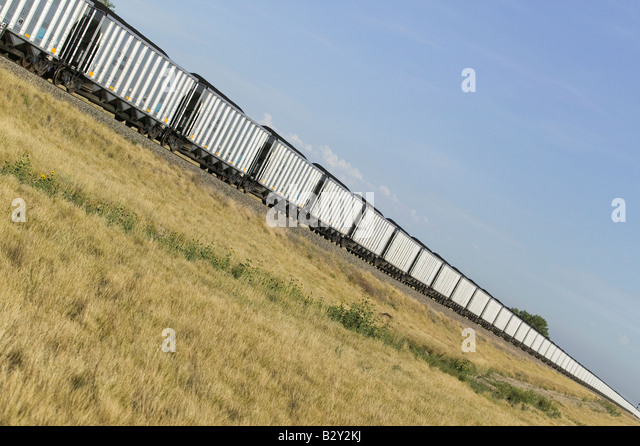 Diagonal view of freight train with coal moving through western Nebraska landscape - Stock Image
