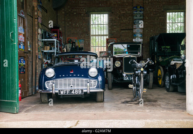 1958 Triumph TR3 and other classic cars in a garage at Bicester Heritage Centre. Oxfordshire, England - Stock Image