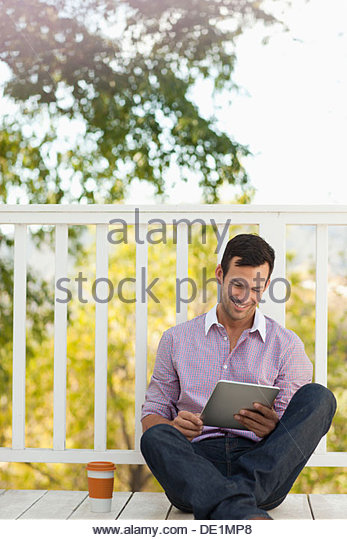 Man using tablet computer outdoors - Stock Image