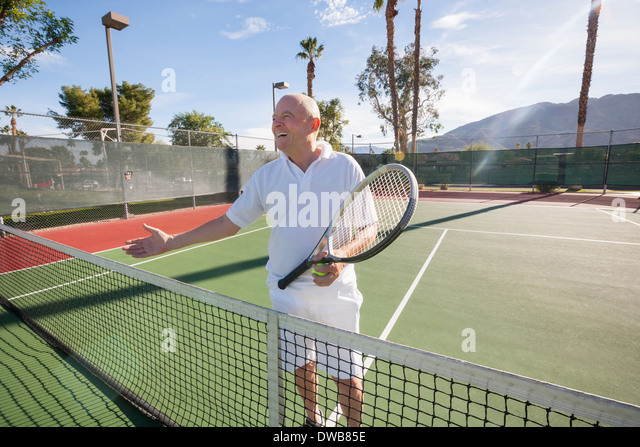 Happy senior male tennis player offering handshake on court - Stock Image