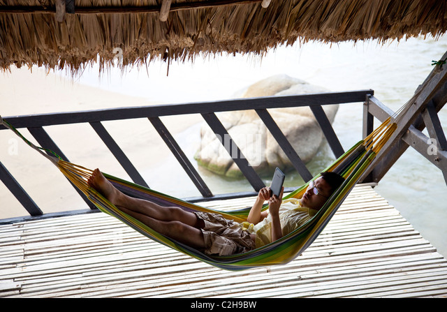 Tourist relaxing in a hammock and reading a Kindle next to the ocean in Colombia - Stock Image