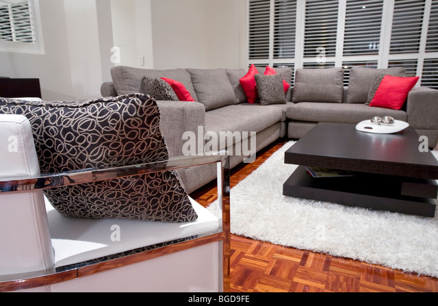 modern living room interior with charcoal sofa and chocolate brown coffee table - Stock Image