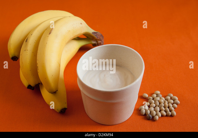 Close-up view of organic Banana Soy Yogurt with Banana bunch and Soybeans - Stock Image
