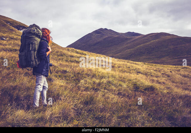 young woman backpacking through wilderness with mountains - Stock Image