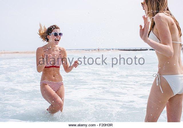Two young female friends wearing bikinis splashing in sea - Stock Image