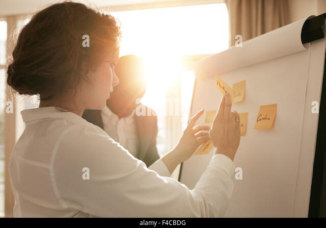 Shot of young business professionals brainstorming in a meeting. Businesswoman and businessman presenting their - Stock Image