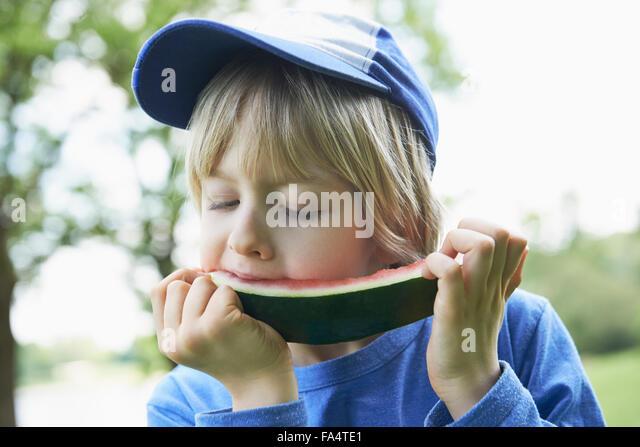 Boy enjoying slice of watermelon at picnic, Munich, Bavaria, Germany - Stock-Bilder
