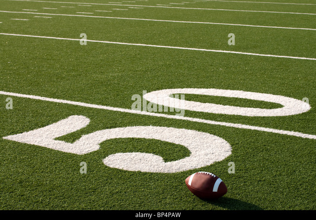 American football on field next to 50 yard line. - Stock Image
