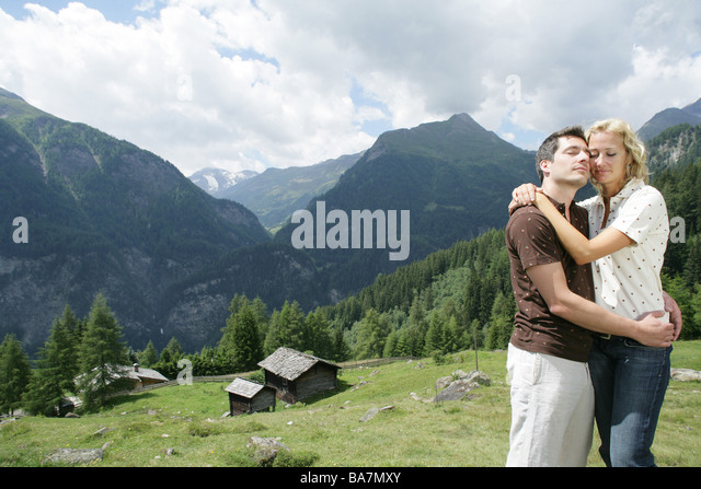 Young couple embracing each other on alp, Heiligenblut, Hohe Tauern National Park, Carinthia, Austria - Stock Image