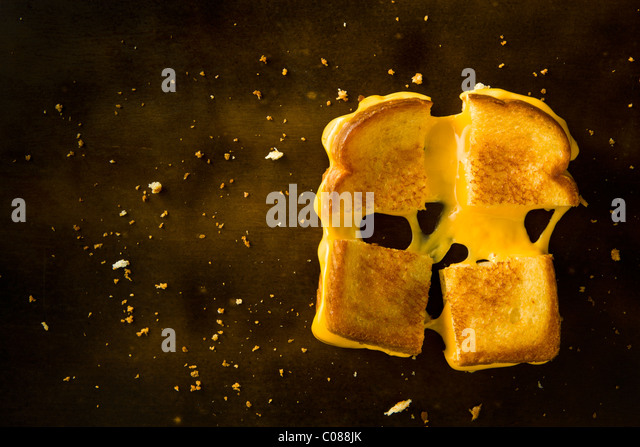 A Grilled Cheese Sandwich cut in four squares pulling the cheese on a wood table - Stock Image