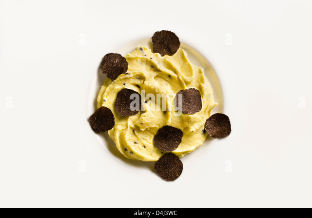 Potato purée with Black Truffles on a white plate. - Stock Image