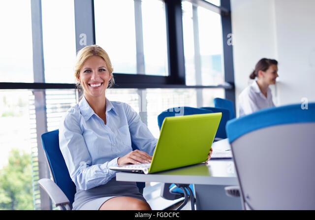 business woman with her staff in background at office - Stock Image