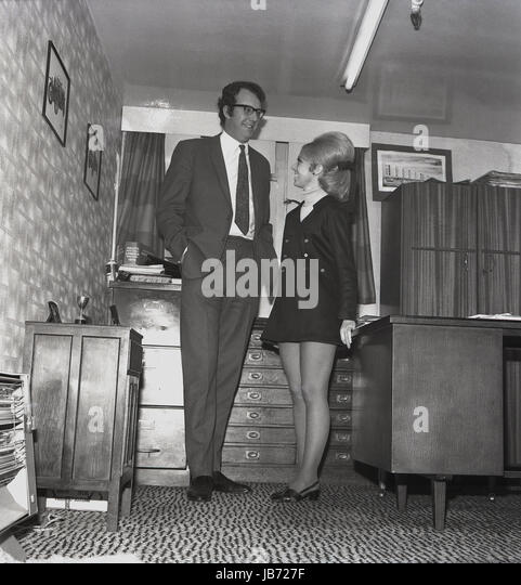 1970s, historical, a secretary wearing a mini-skirt and with a buoffant hairdo stands next to her tall male boss - Stock Image