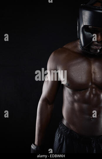 Muscular body of African male boxer against black background with copy space. Cropped image of male in boxing gear. - Stock Image