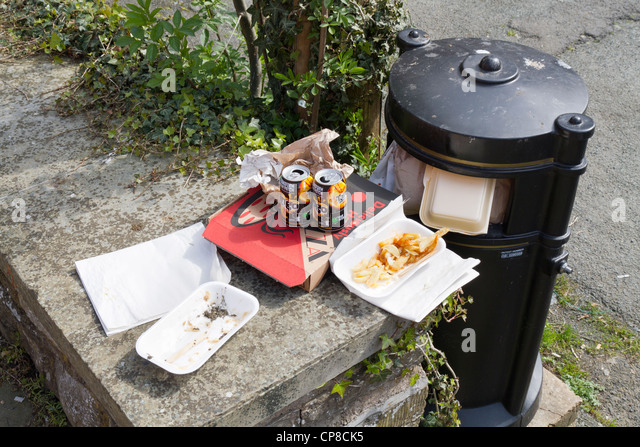 Food waste and litter next to a full litter bin - Stock Image