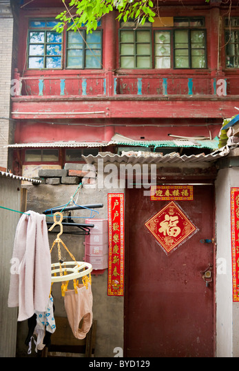 Door to house in the Hutong, Beijing, China with drying washing hanging outside. JMH4843 - Stock Image