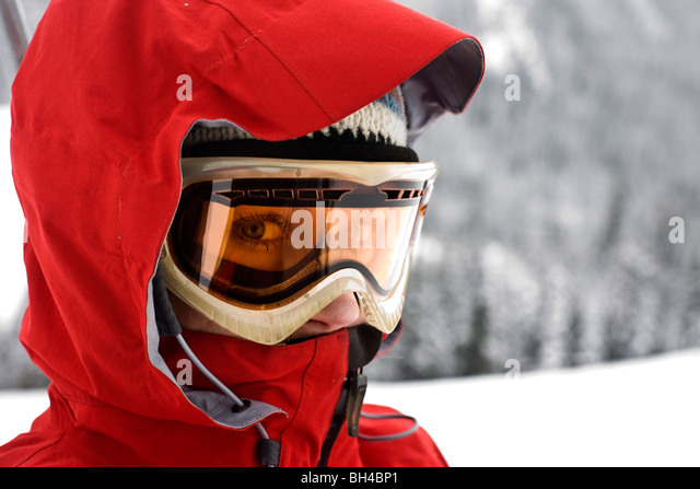 A close-up portrait of a woman wearing a red ski coat, goggles and ski cap looking directly into camera with just - Stock Image