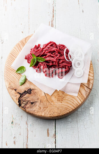 Fresh minced meat with onion on wooden cutting board on blue background - Stock Image