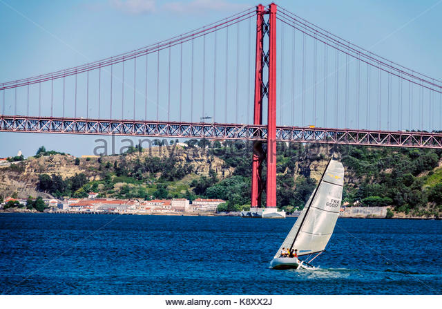 Portugal Lisbon Belem Tagus River Ponte 25 de Abril 25th of April Bridge suspension tower sailboat sailing view - Stock Image