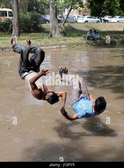Lahore. 17th Apr, 2017. Pakistani men jump into a canal to cool themselves off during heat wave in eastern Pakistan's - Stock Image