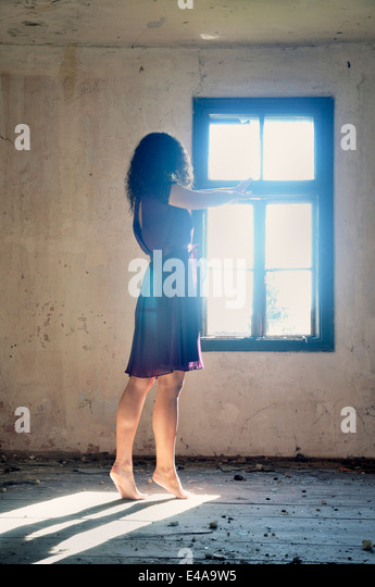 Young woman standing by the window reaching for the light - Stock Image