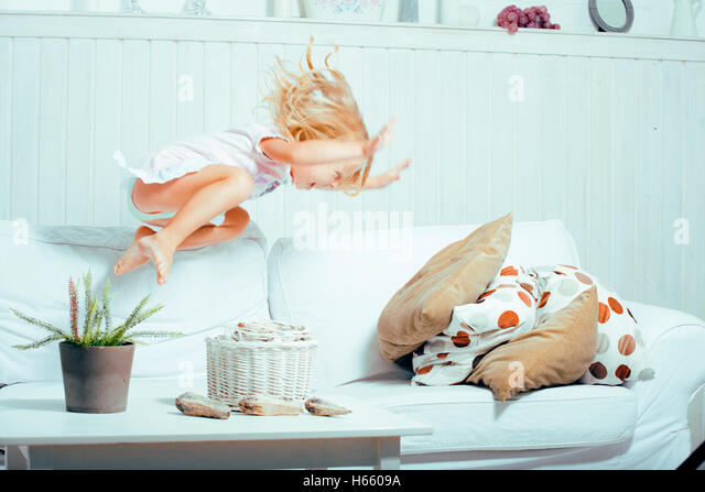 little cute blonde norwegian girl playing on sofa with pillows, crazy home alone, lifestyle people concept - Stock Image