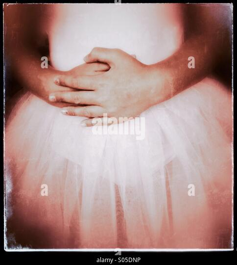 Young ballet dancer dressed in a tutu and with her hands folded in front of her. - Stock Image