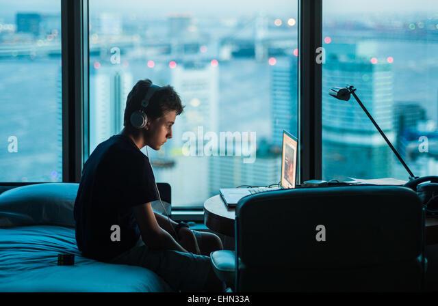 Teenage boy using a laptop. - Stock Image
