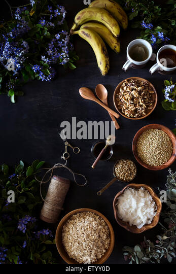 Ingredients for Banana Bread Granola are displayed on a dark surface, surrounded by fresh spring flowers. - Stock Image